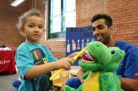 A Penn Dental Student teaches a toddler how to brush teeth at the EHS Health Fair